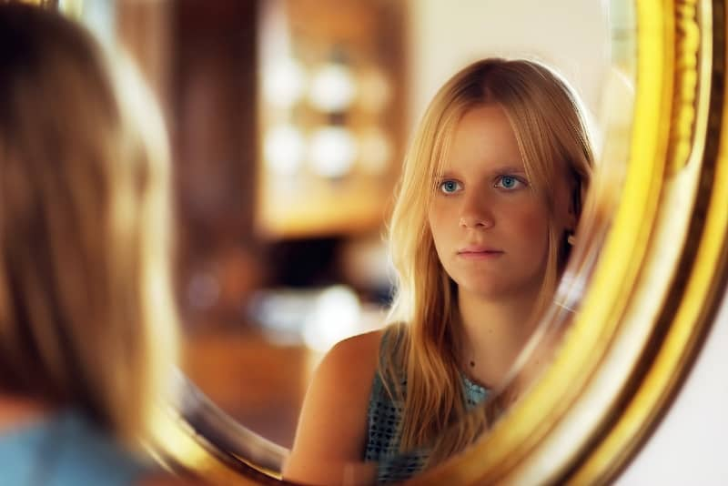blonde woman with blue eyes looking at mirror