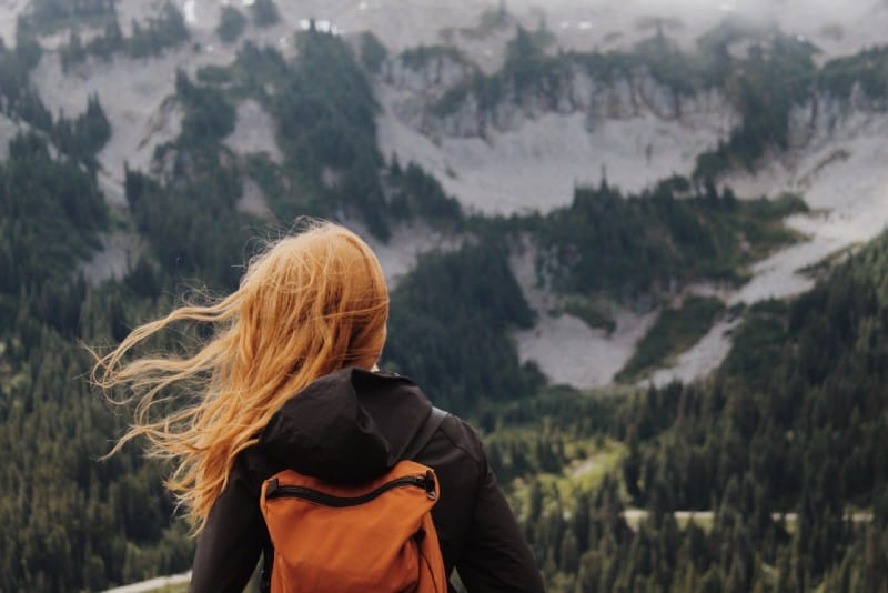 woman with orange backpack looking at mountains during daytime