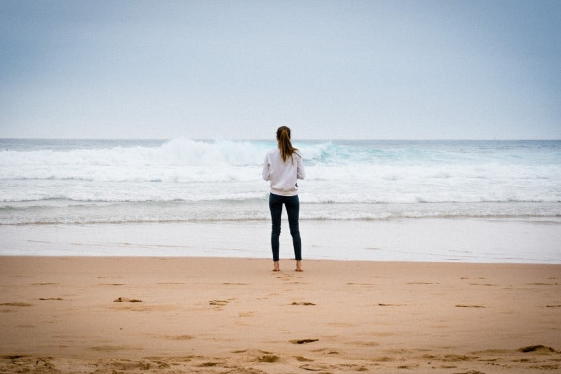 woman in white sweatshirt standing on beach and looking at ocean