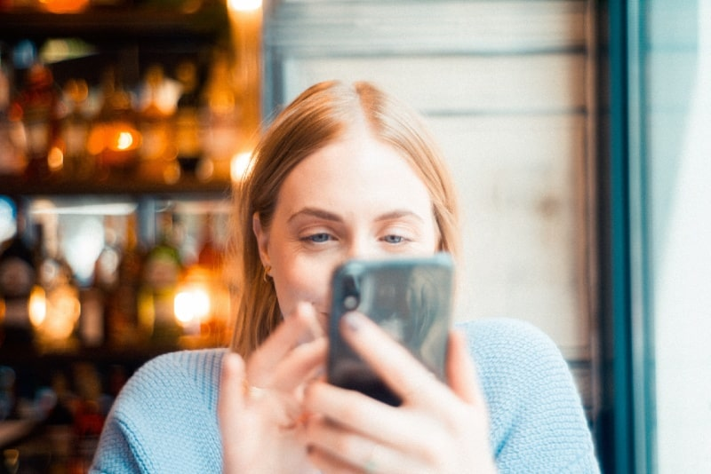 woman in blue sweater looking at smartphone