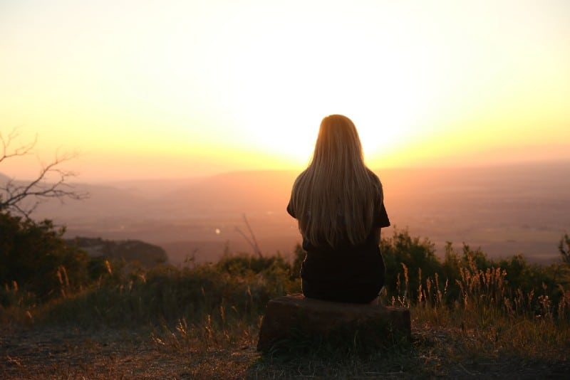 blonde woman sitting on rock and looking at sunset