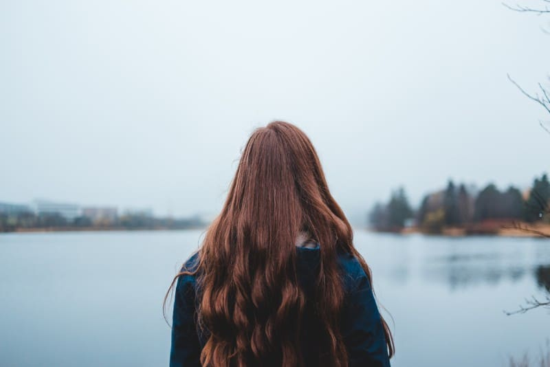 woman with long hair looking at water