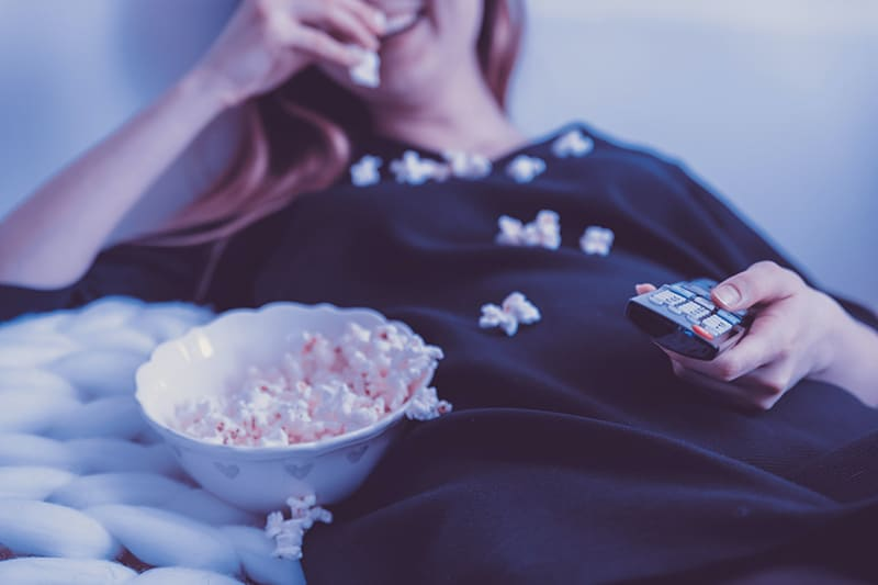 woman lying on bed holding remote control while eating popcorn