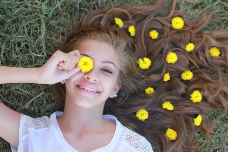 woman lying on grass holding yellow flower