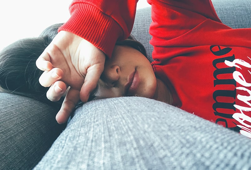 woman lying on grey couch while covering her eyes with hand