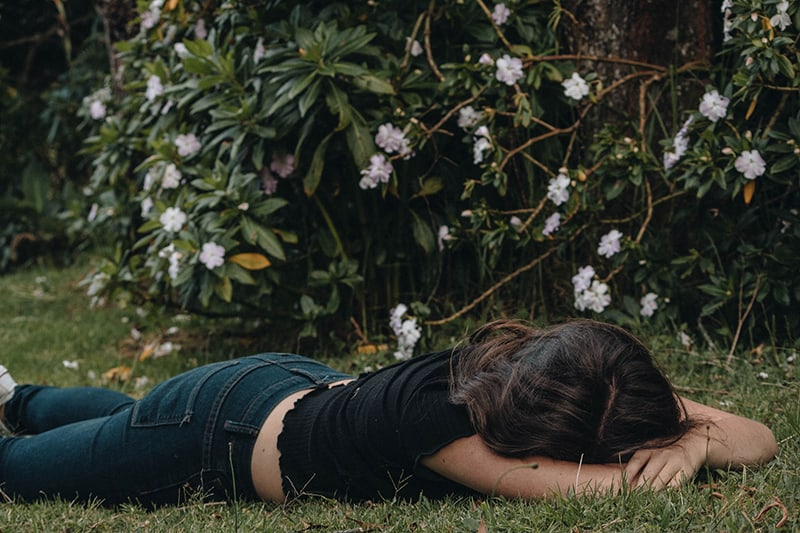 woman lying on the grass near flower bush
