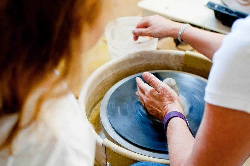 woman in white shirt making pottery