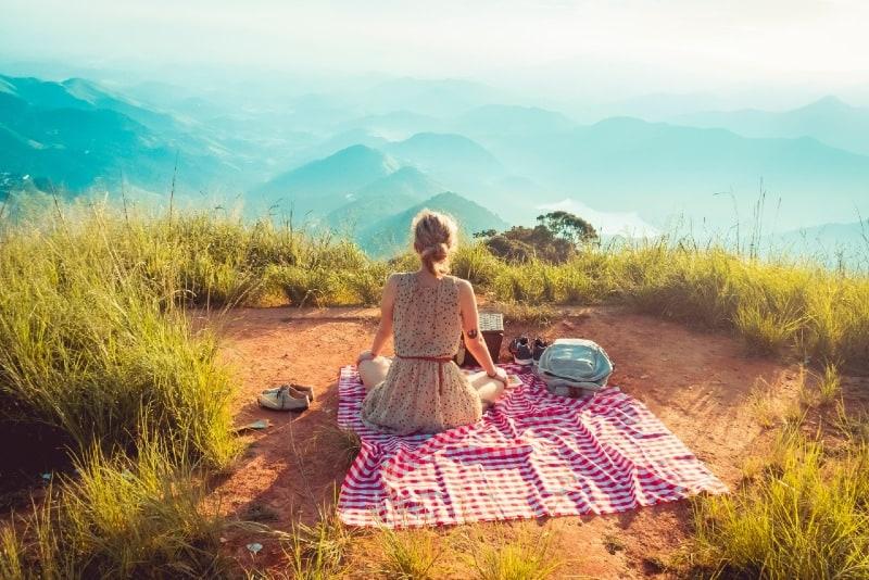 woman in sleeveless dress sitting on picnic mat