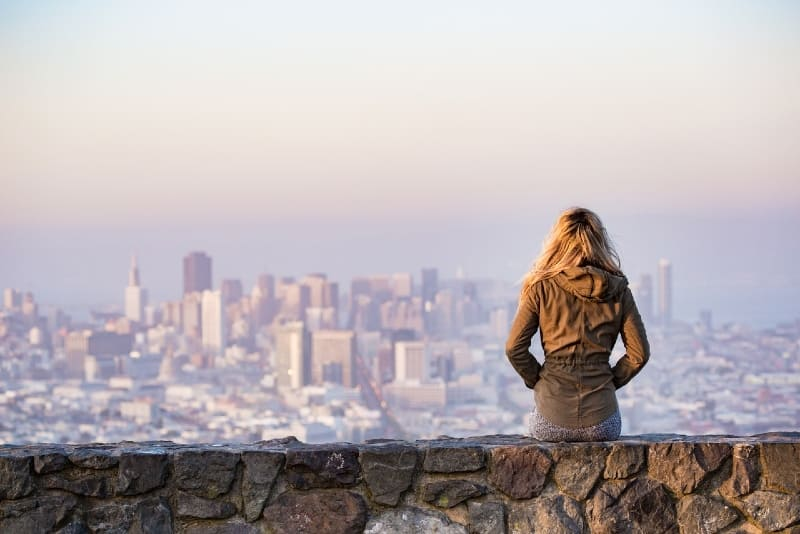blonde woman sitting on rock looking at city