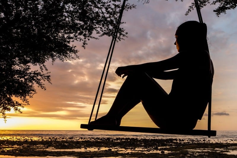 silhouette of woman sitting on swing during golden hour