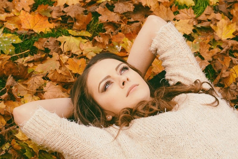 woman on the leaves lying while thinking