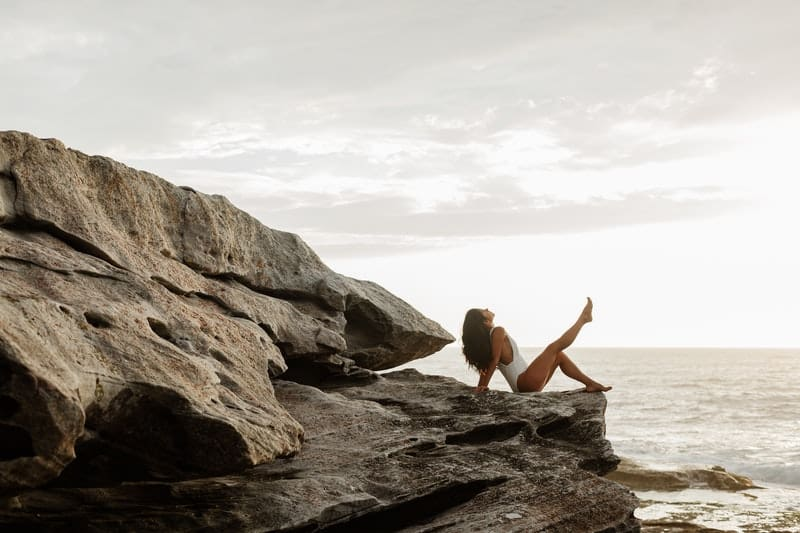 woman on swimwear sitting on rocks near the a body of water with one leg raised