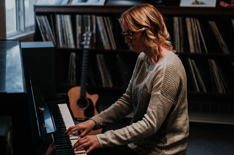 woman playing the piano guitar bookshelves background