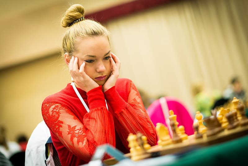 Woman in red playing chess