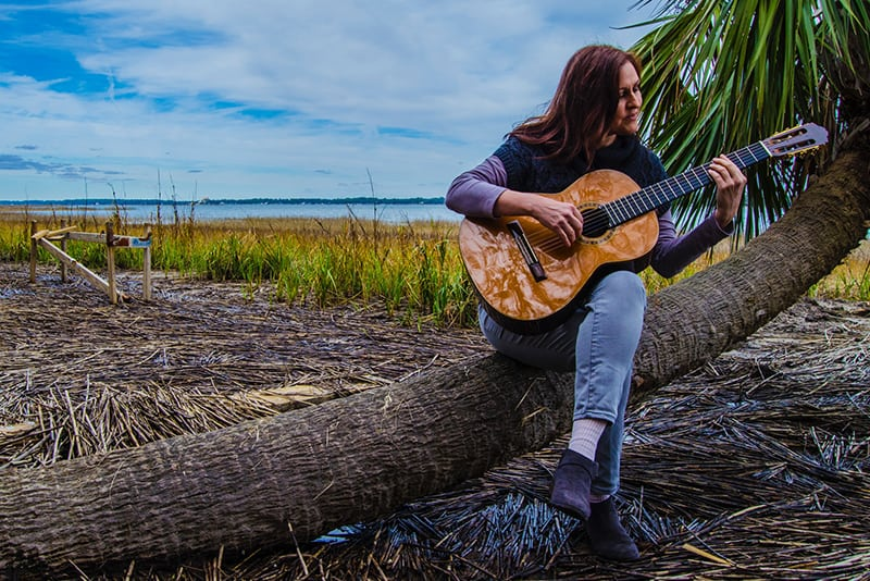 man playing classical guitar while sitting on coconut tree