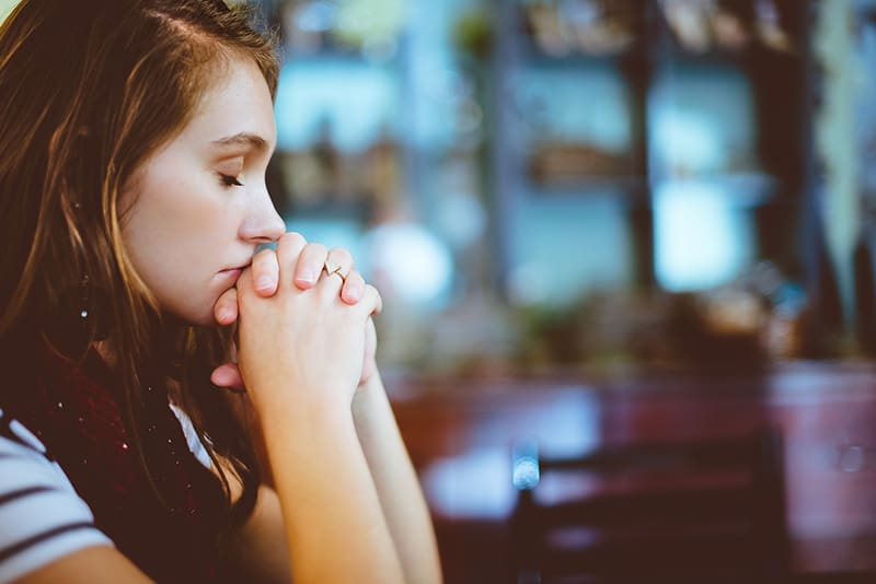 woman praying with closed eyes
