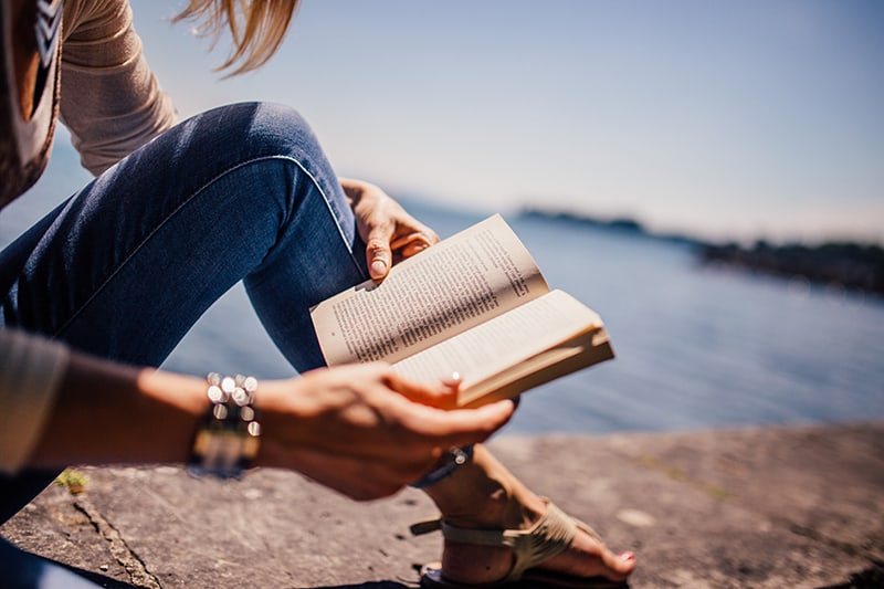 woman reading a book while sitting beside body of water