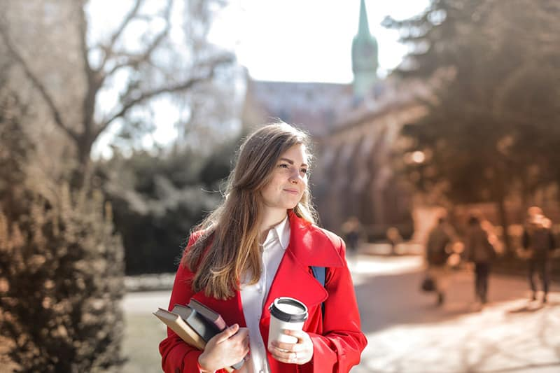 Woman wearing red coat and holding her books and a coffee cup