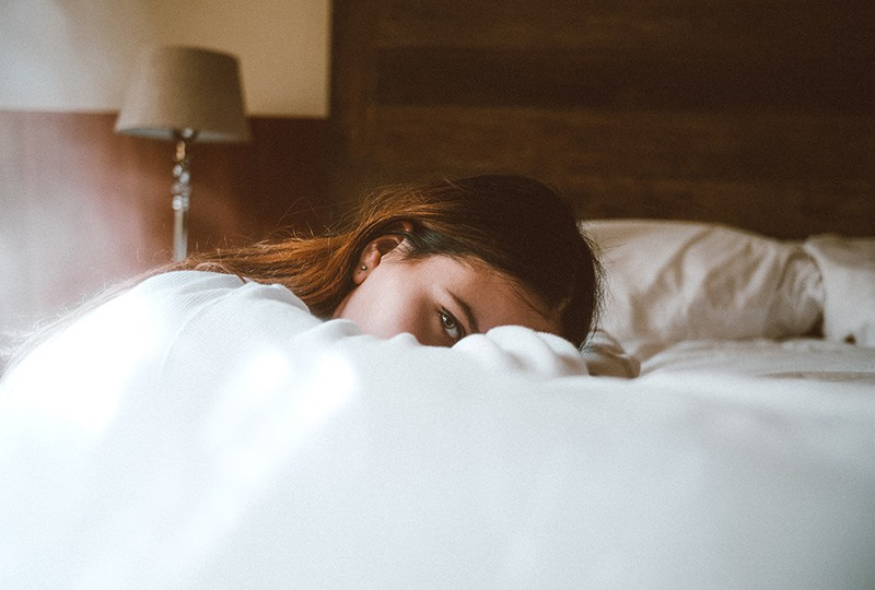 woman resting her head on bed during daytime