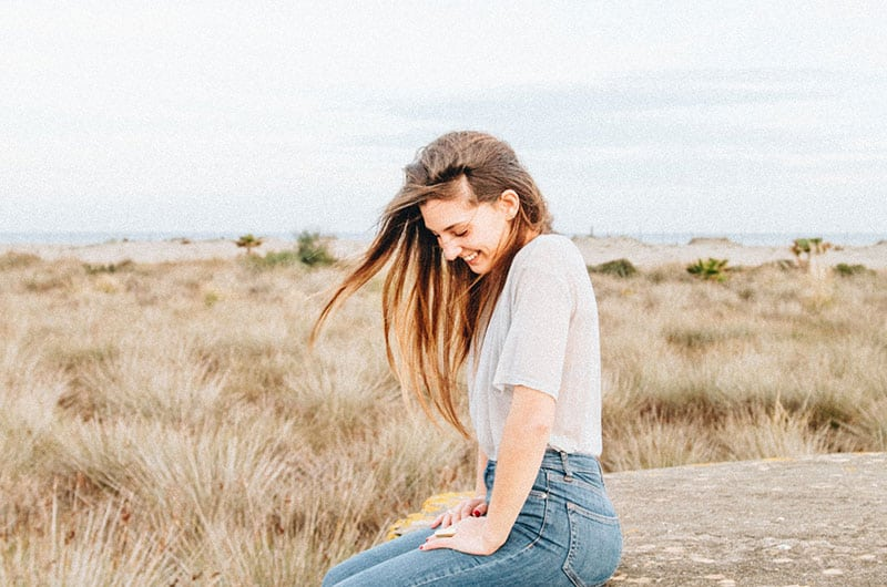 Woman by the ricefields wearing white top and jeans