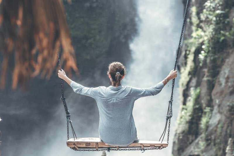 woman riding big swing in front of the waterfalls