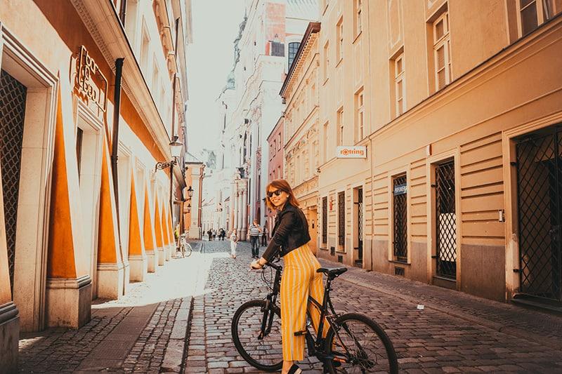 woman riding black bike in empty street