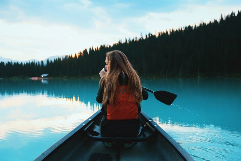 blonde haired woman with red backpack riding on boat