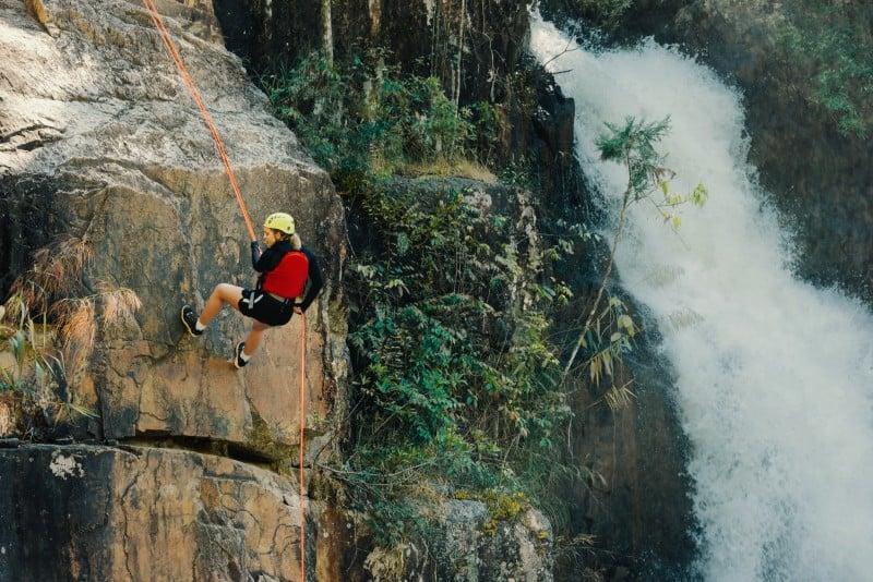 woman wearing helmet rock climbing near waterfall