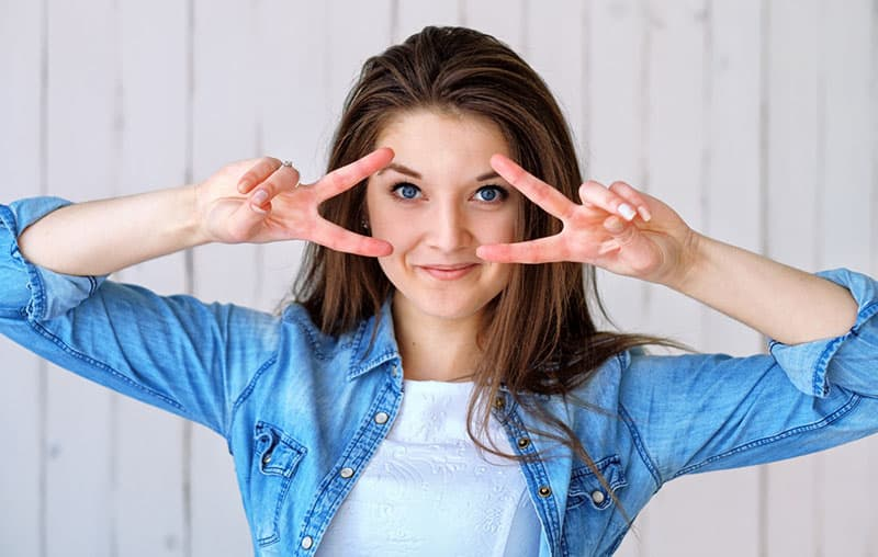 woman showing hand sign of two peace sign near her eyes