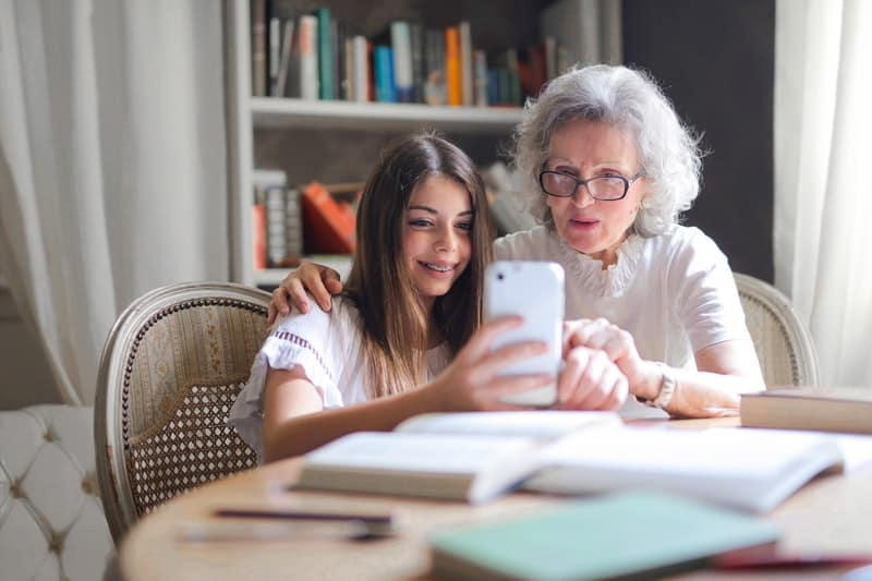 woman showing her cellphone to an old woman while on the table