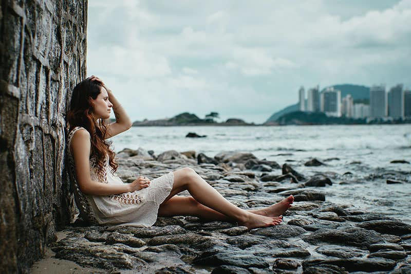 woman sitting in the rocks beside a body of the water leaning a wall