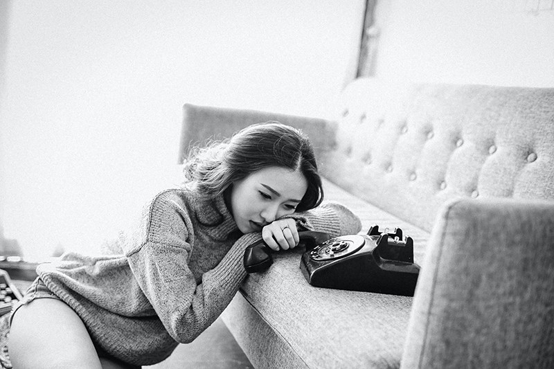 woman sitting near the sofa while holding telephone handset