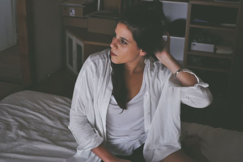 woman in white shirt sitting on bed touching her hair