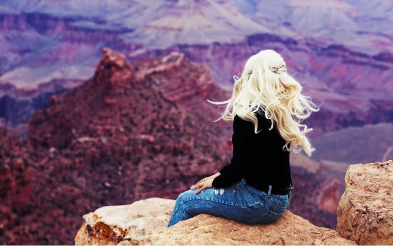 Blonde woman sitting on brown cliff admiring the view during daytime