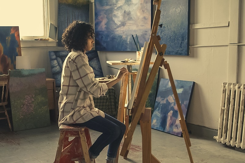 woman sitting on brown stool while painting