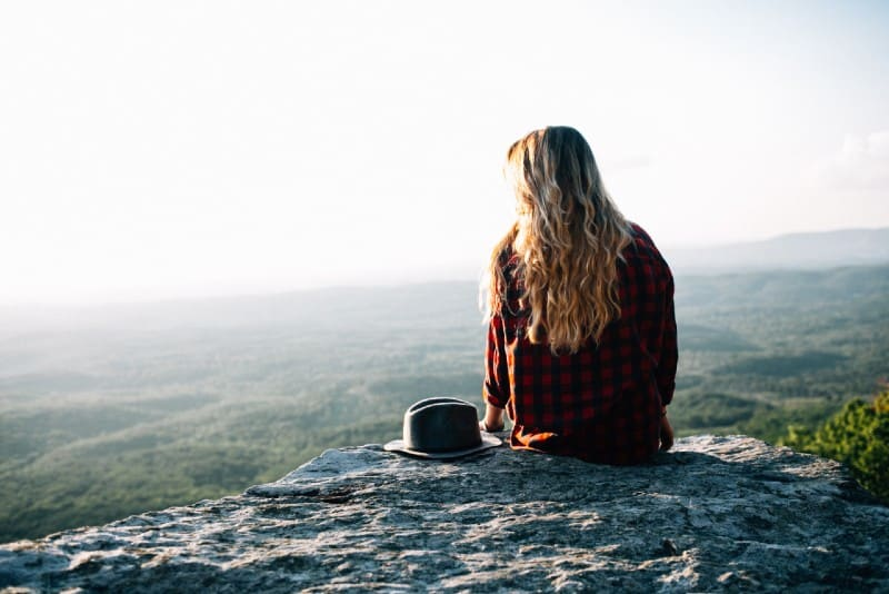 blonde woman in checked shirt sitting on cliff