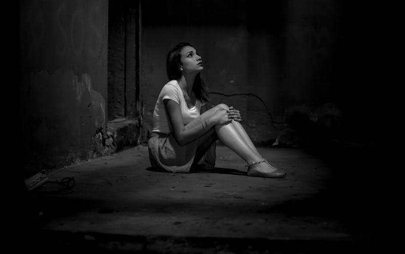 black and white photo of sad woman sitting on floor