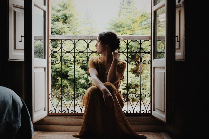 woman in maxi dress sitting on floor near window