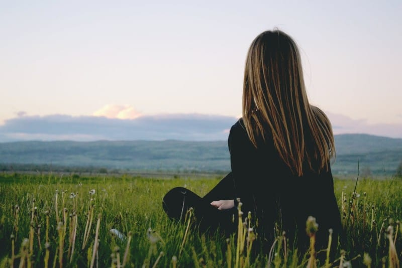 woman in black shirt sitting on grass looking at mountain