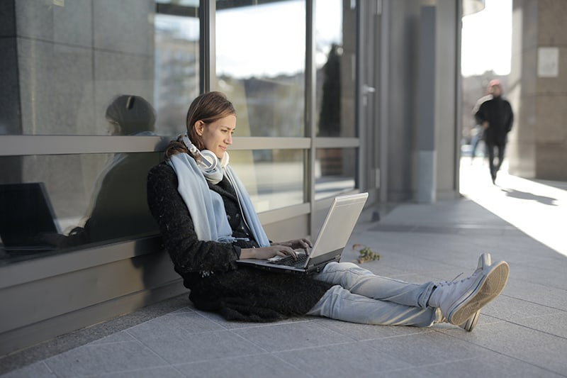 woman sitting on gray concrete floor and using laptop