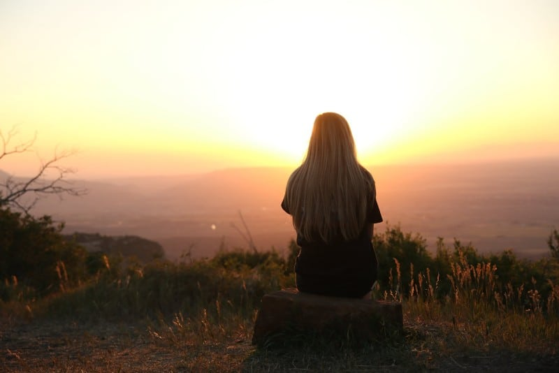 blonde woman sitting on rock looking at sunset