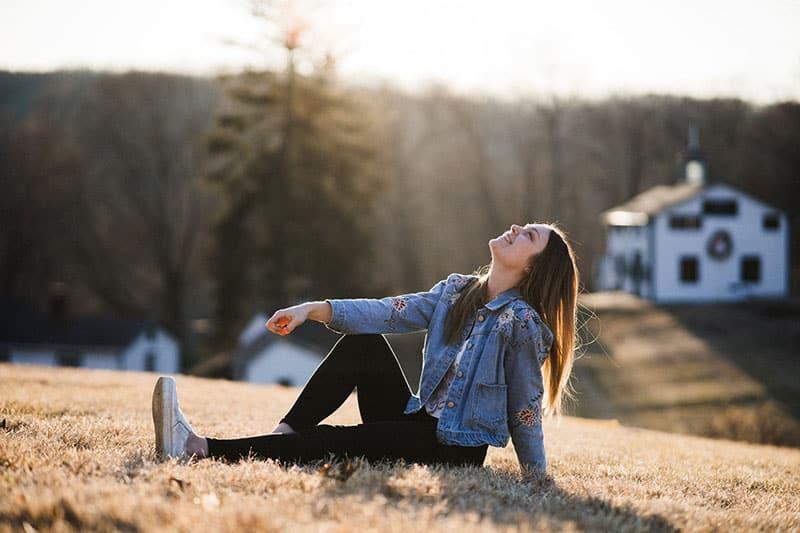 woman sitting on the ground smiling wearing denim jacket