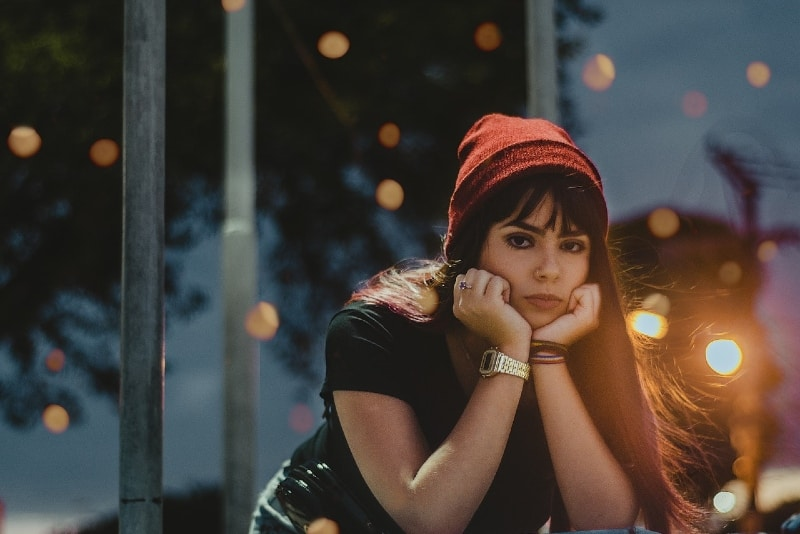woman in red knit cap sitting outdoor