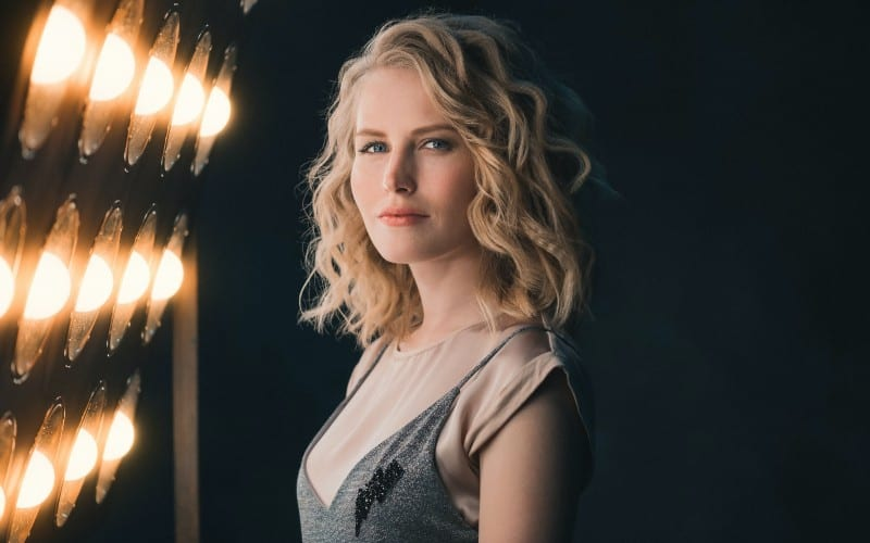 Young blonde woman standing beside lights