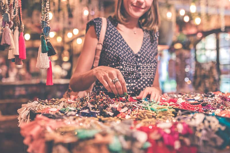 woman standing beside table full of accessories