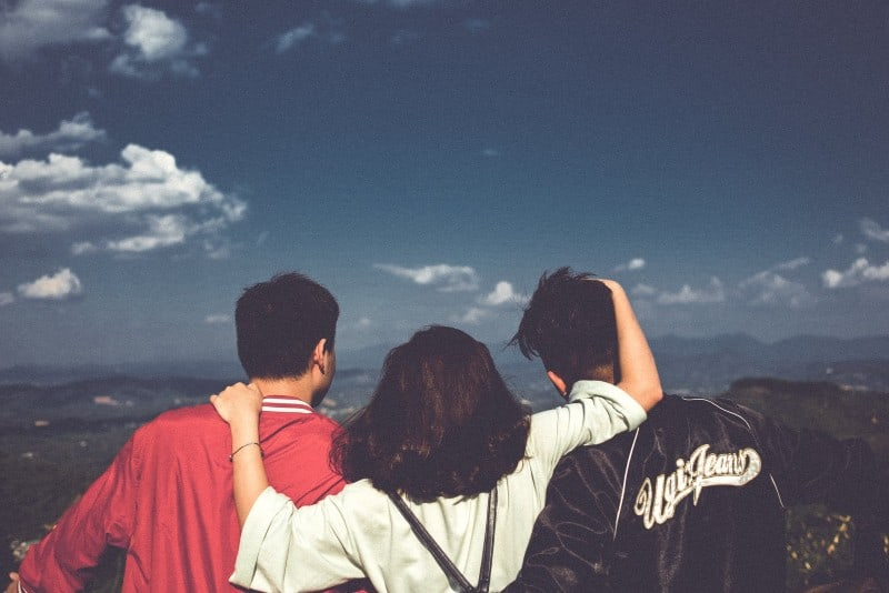 woman standing between men and looking at mountain