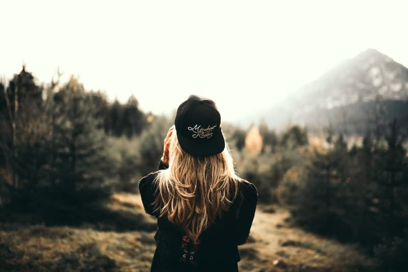 blonde woman with cap standing in forest
