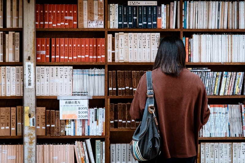 woman in brown shirt standing in front of library books