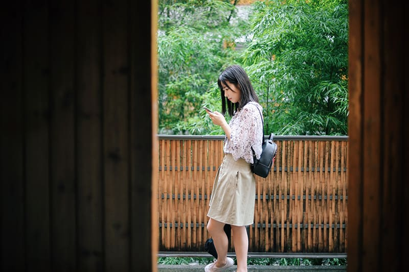 woman standing near brown and black wooden balcony while using smartphone