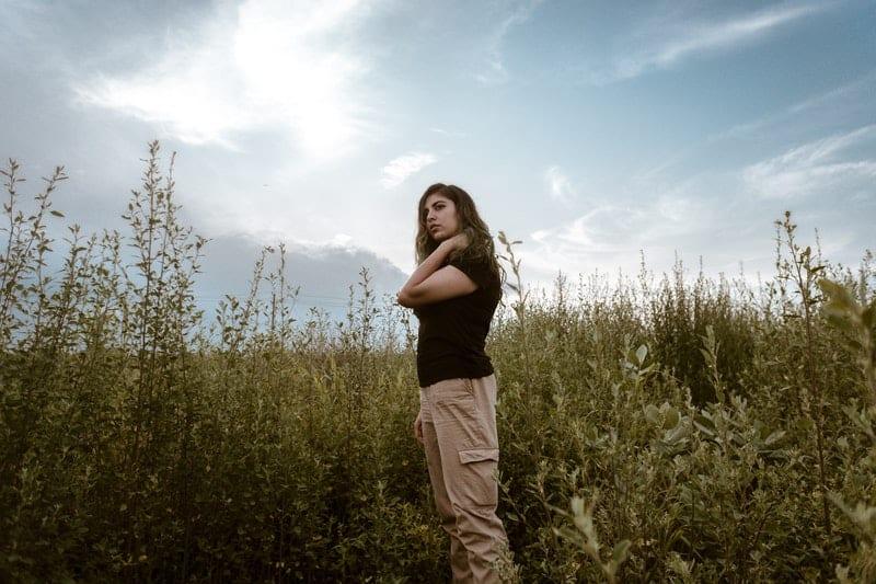 woman standing near tall grass